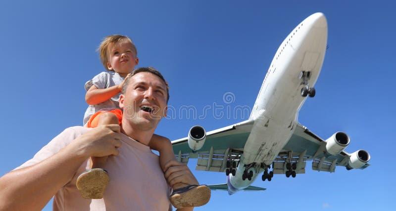 Père et fils observant l'avion de débarquement images stock