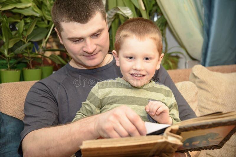 Père et fils observant un album photos de famille, Ukreina photo stock