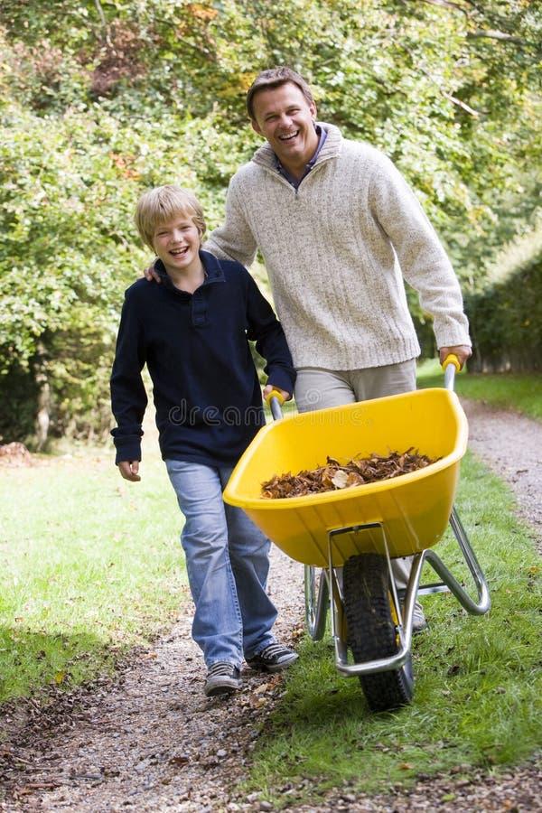 Père et fils poussant la brouette photos libres de droits