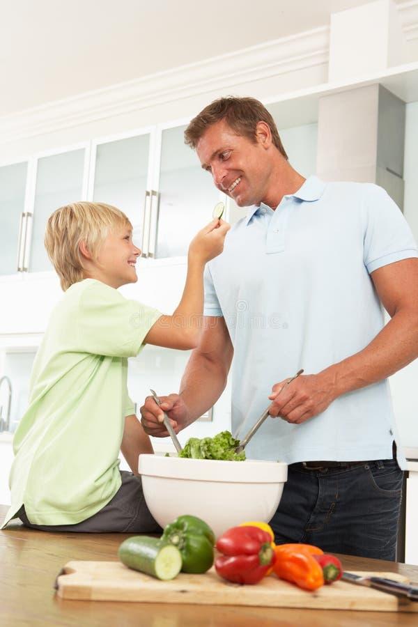 Père et fils préparant la salade dans la cuisine moderne photos stock