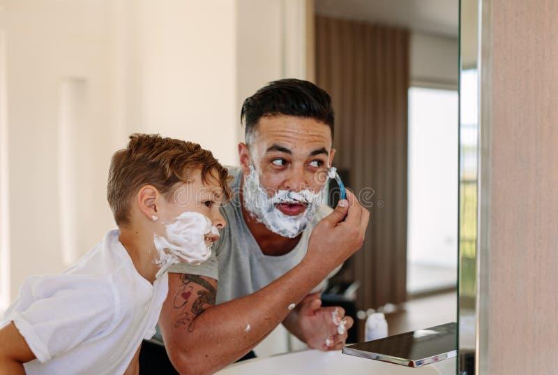 Père et fils rasant ensemble dans la salle de bains photos stock
