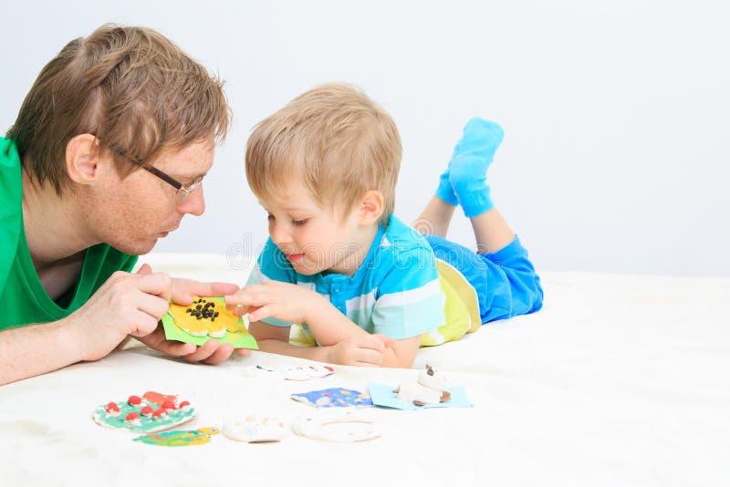 Père et fils regardant des métiers de bébé image libre de droits