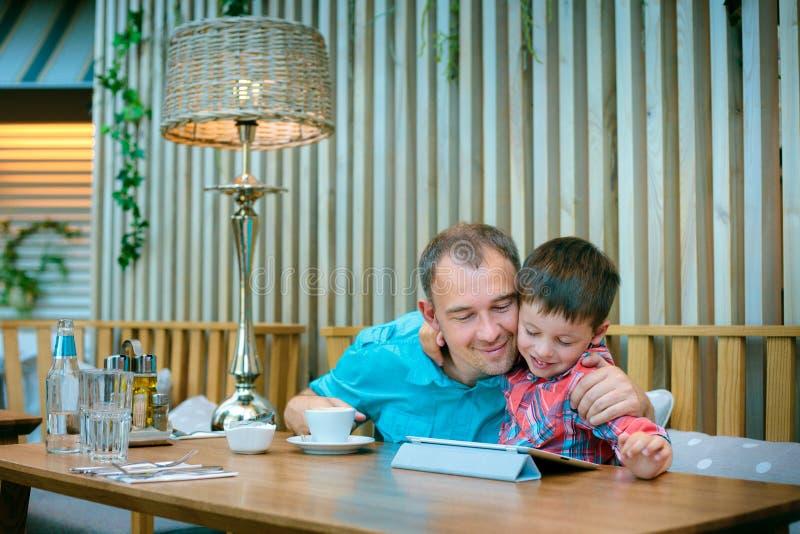 Père et fils regardant l'écran d'ordinateur portatif en café photographie stock libre de droits
