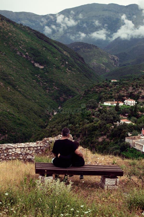 Père et fils s'asseyant contre des montagnes Concept de jour de pères photo stock