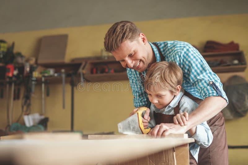 Père et fils sciant une planche images libres de droits