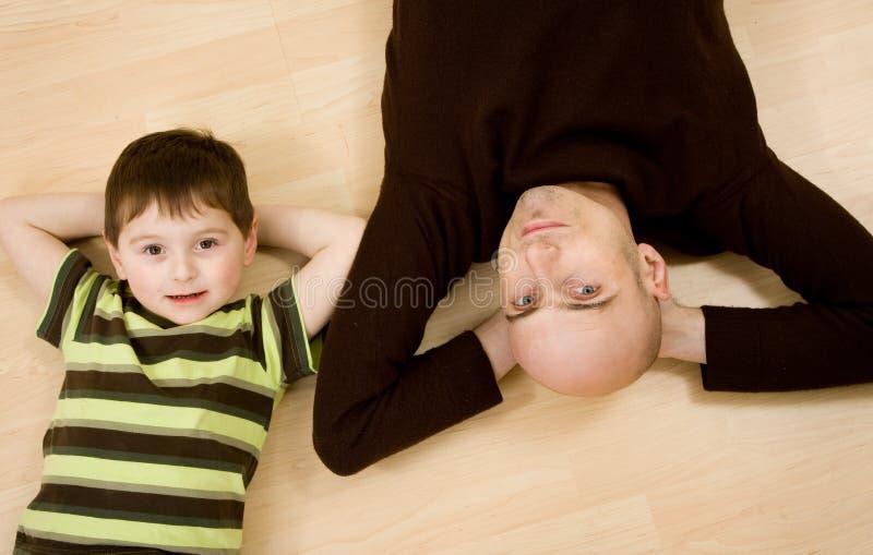 Père et fils se couchant photographie stock
