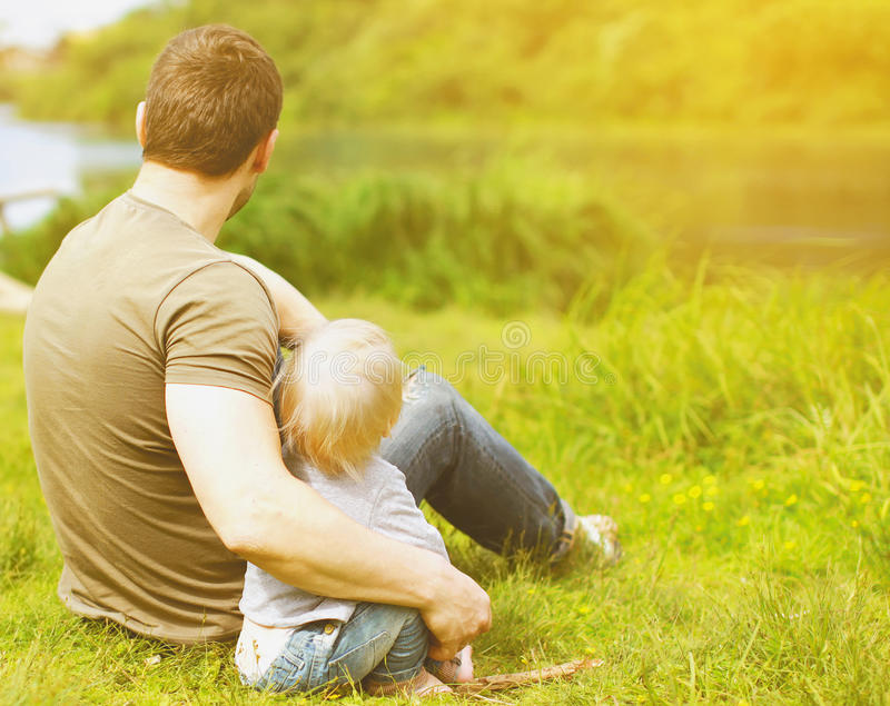 Père et fils se reposant sur la nature photos stock