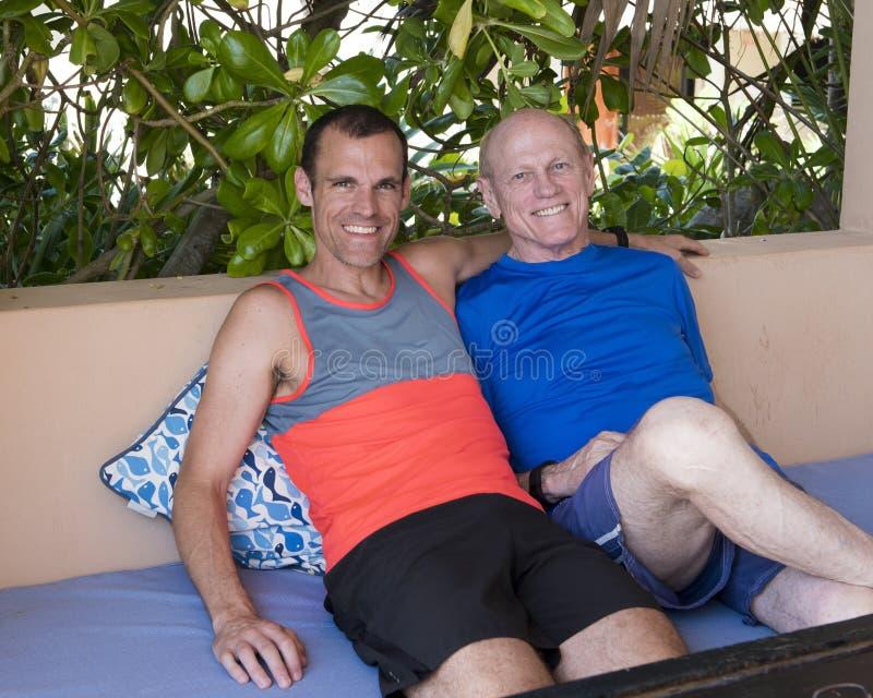 Père et fils, souriant sur un banc extérieur photographie stock libre de droits