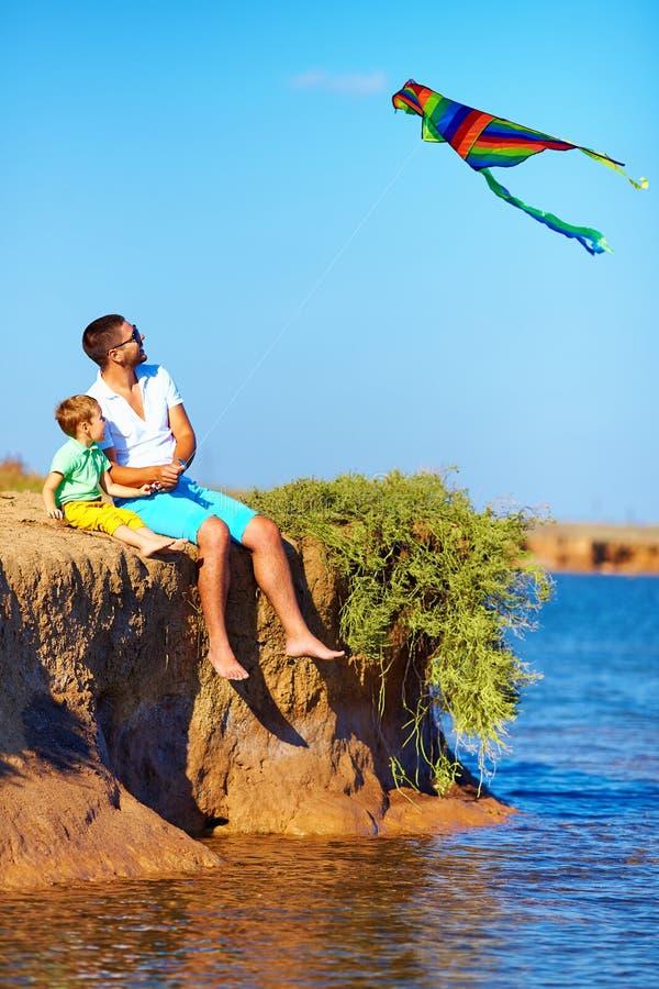 Père et fils sur la falaise jouant avec le cerf-volant image stock