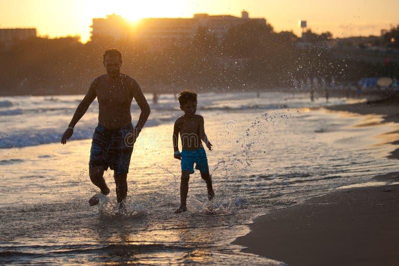 Père et fils sur la plage au coucher du soleil photographie stock