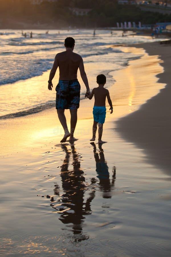 Père et fils sur la plage au coucher du soleil photos stock