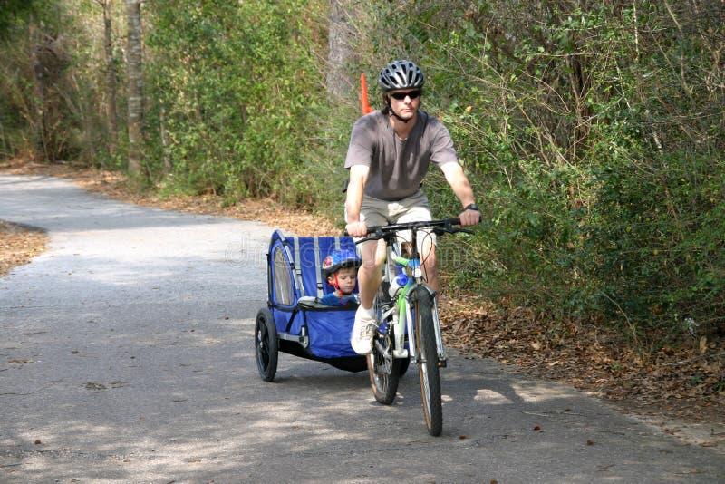 Père et fils sur le journal de vélo images stock