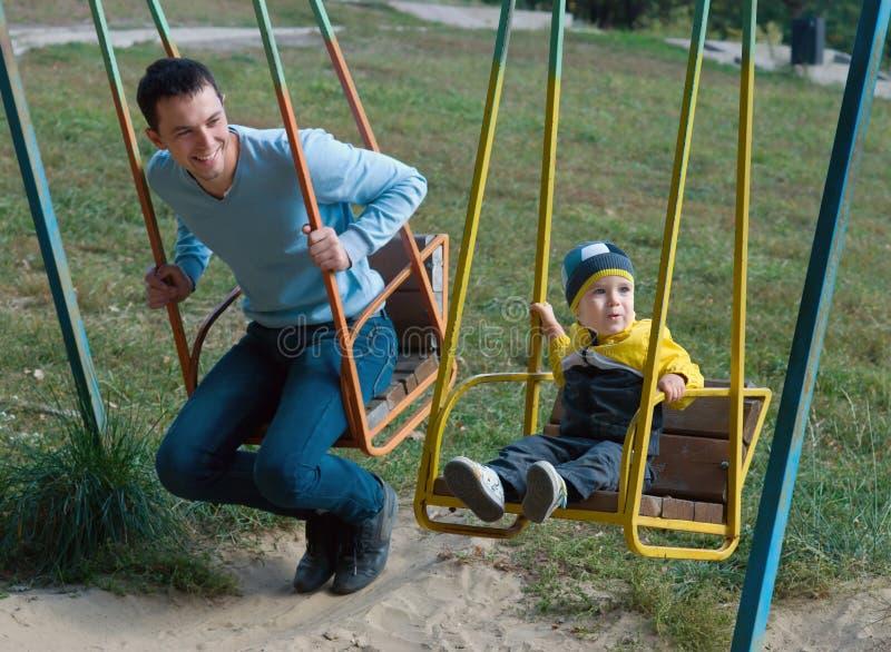 Père et fils sur une oscillation images libres de droits