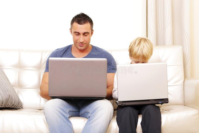 Père et fils travaillant sur leurs ordinateurs sur le sofa image libre de droits