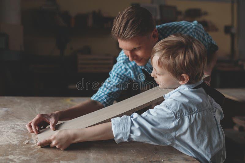 Père et fils travaillants à l'intérieur image stock