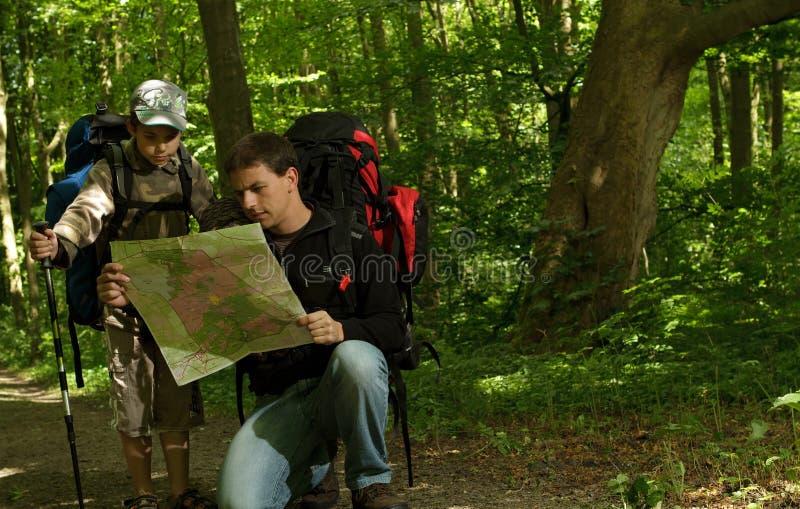 Père et fils trimardant dans la forêt photo stock
