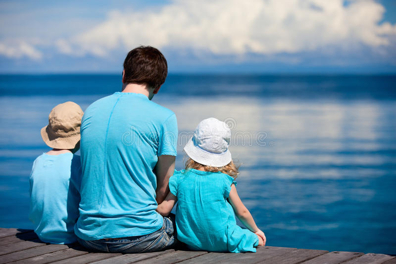 Père et gosses s'asseyant sur le dock en bois images stock