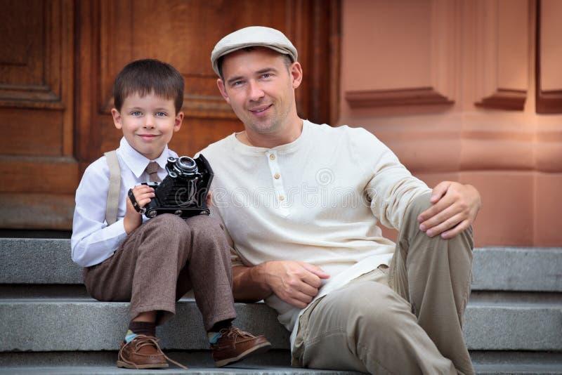 Père et petit fils avec le rétro appareil-photo dehors photos stock