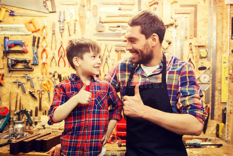Père et petit fils composant des pouces à l'atelier photo stock