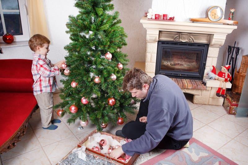 Père et petit fils décorant l'arbre de Noël à la maison photographie stock