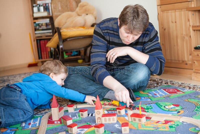Père et petit fils jouant avec le jouet ferroviaire en bois photo libre de droits