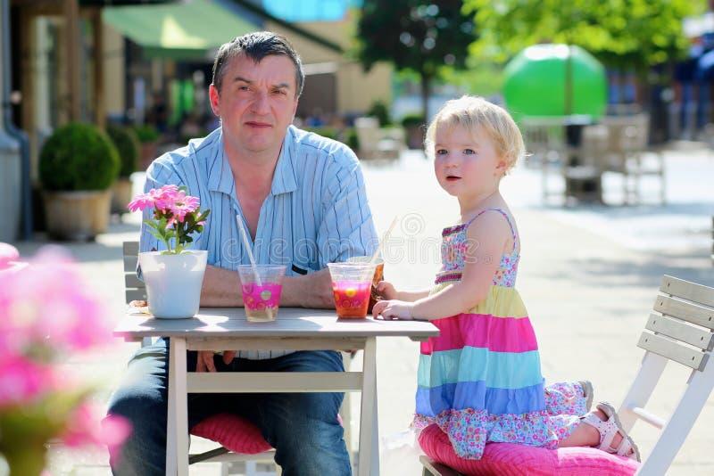 Père et petite fille buvant en café images stock