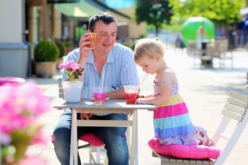 Père et petite fille buvant en café photographie stock libre de droits
