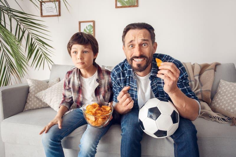 Père et peu de fils à la maison s'asseyant sur le football de observation de boule de participation de puce de consommation de so photographie stock libre de droits
