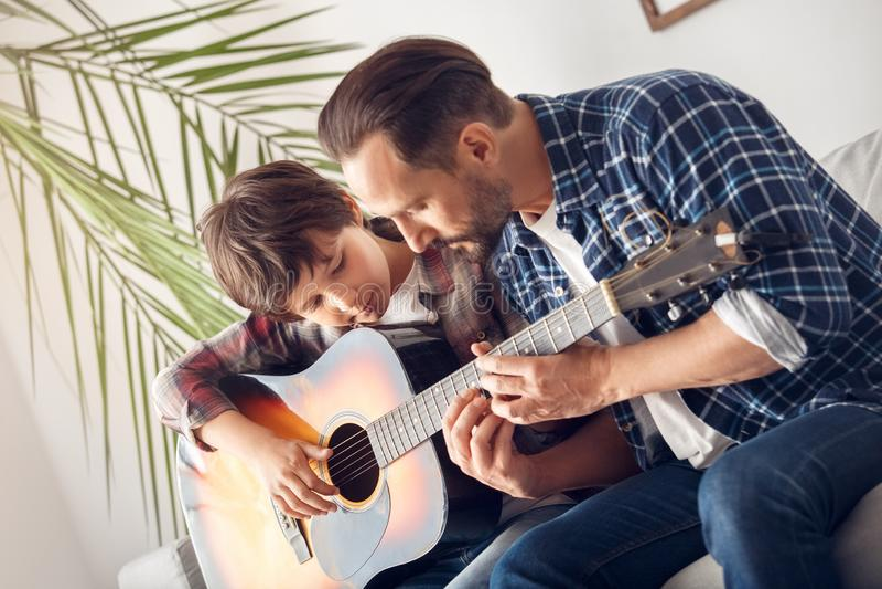 Père et peu de fils à la maison s'asseyant sur le garçon de sofa avec le papa de guitare montrant des cordes réfléchies images stock
