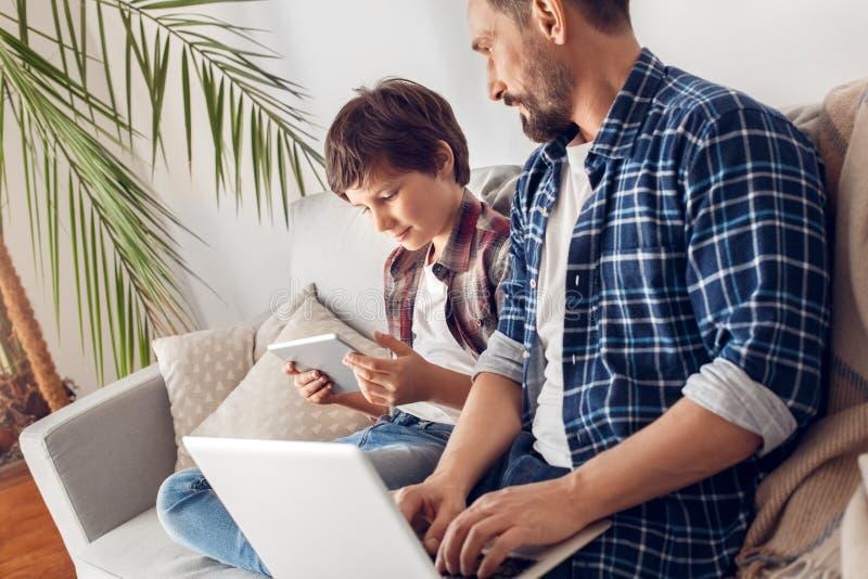Père et peu de fils à la maison s'asseyant sur le papa de sofa travaillant sur l'ordinateur portable regardant la vidéo de observ image libre de droits