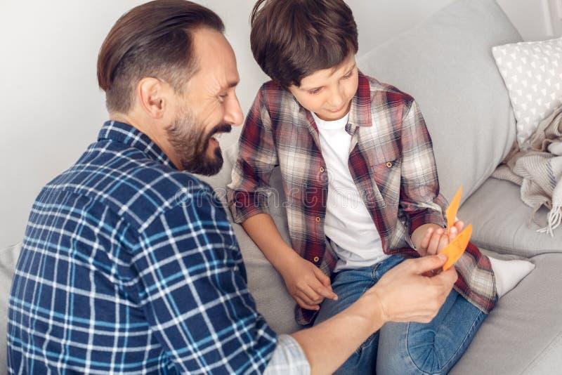 Père et peu de fils à la maison s'asseyant sur le sofa jouant le détective de front regardant rire d'autocollants photos libres de droits