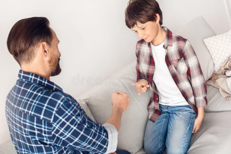 Père et peu de fils à la maison s'asseyant sur le sofa jouant formant la roche et les ciseaux joyeux image stock