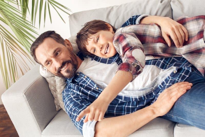 Père et peu de fils à la maison se trouvant sur le sofa étreignant la TV de observation ensemble joyeuse photographie stock