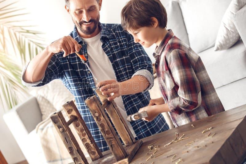 Père et peu de fils à la maison tenant la vis de vissage de papa dans le garçon gai de moment de chaise tenant le marteau photographie stock