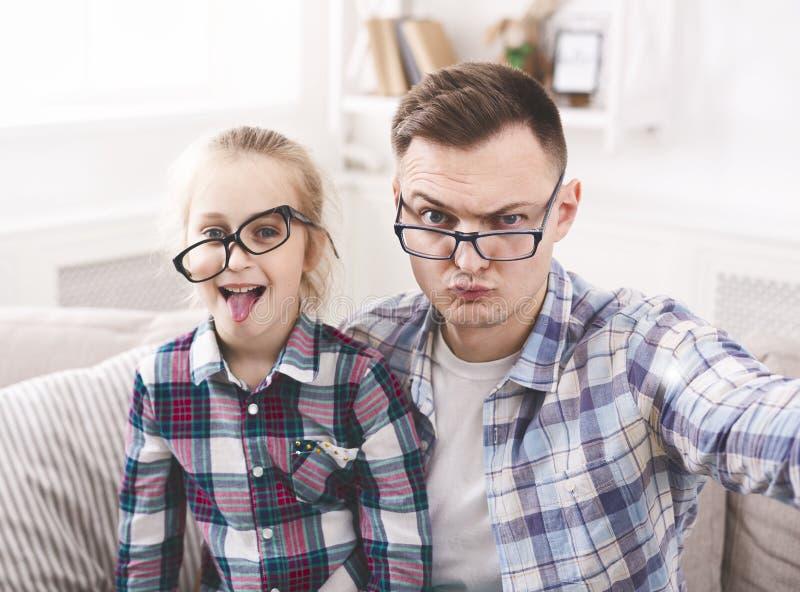 Père et sa petite fille prenant le selfie drôle photo libre de droits