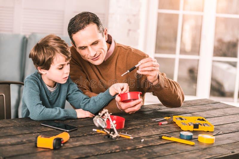 Père futé et fils bricolant avec quelques instruments curieux image libre de droits