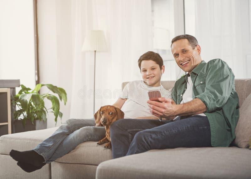Père gai et fils écoutant la musique du smartphone image libre de droits