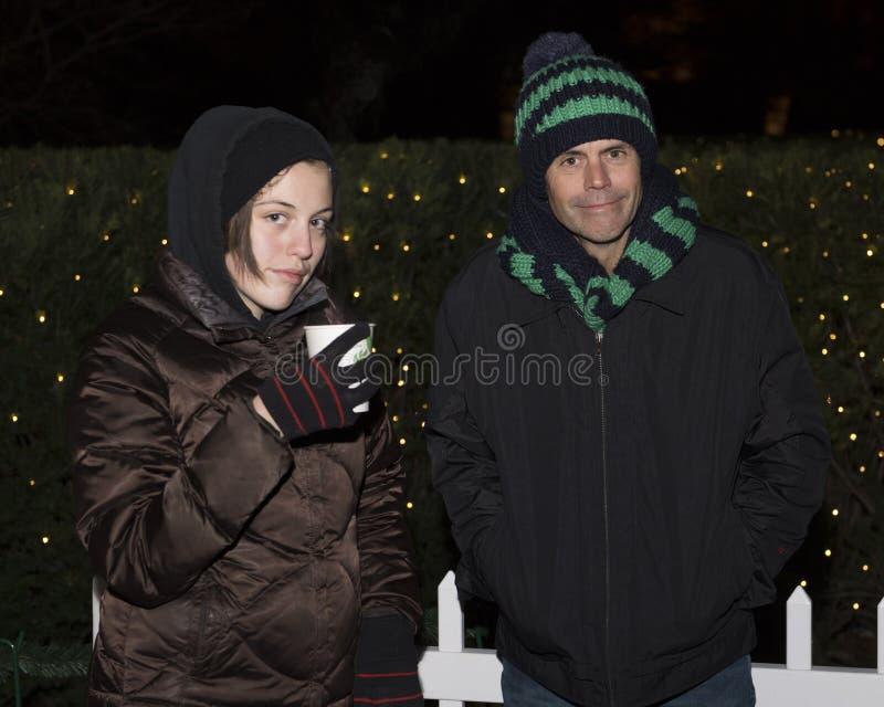 Père grincheux et fille se tenant dans le froid devant des buissons avec des lumières de Noël photographie stock