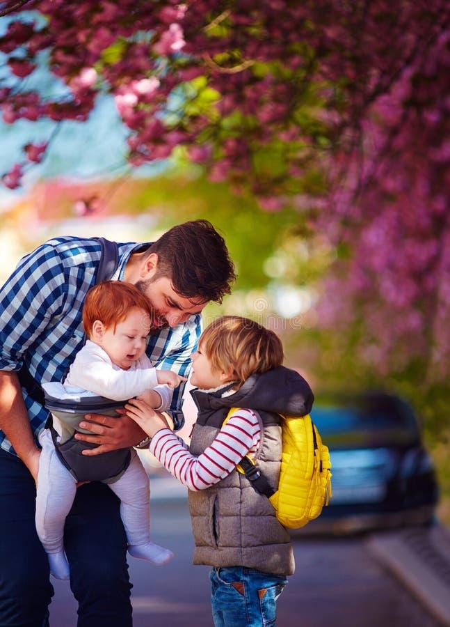 Père heureux avec des enfants sur la ville de promenade au printemps, transporteur de bébé, congé paternel image stock