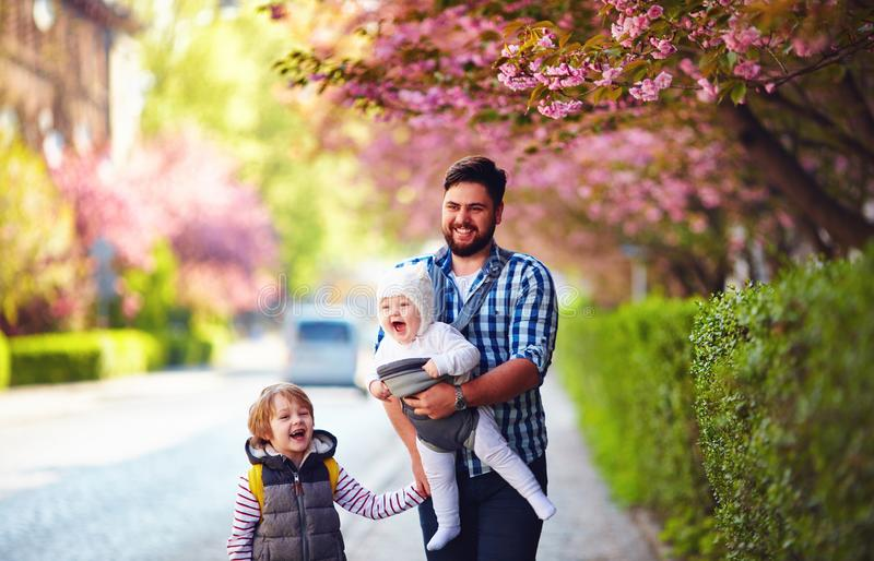 Père heureux avec des enfants sur la ville de promenade au printemps, transporteur de bébé, congé paternel photo libre de droits