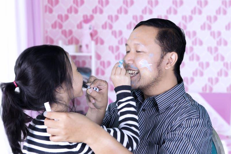 Père heureux avec l'enfant faisant la peinture de visage images stock