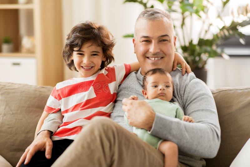 Père heureux avec le fils de préadolescent et de bébé à la maison photo stock