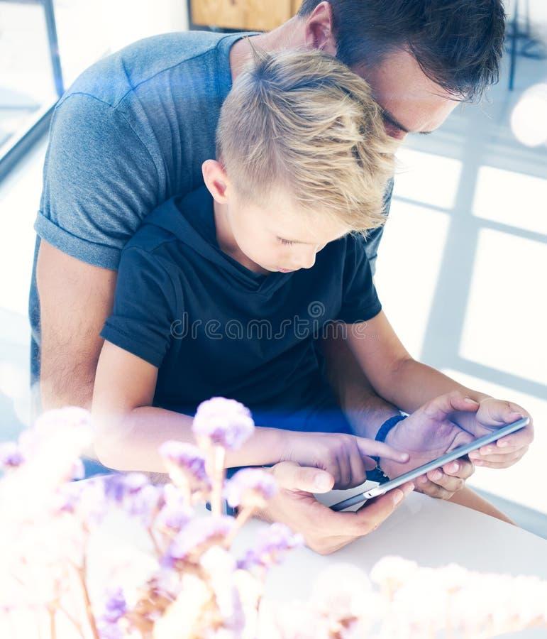 Père heureux avec le jeune fils à l'aide de la tablette dans la chambre ensoleillée Papa et petit garçon jouant le repos d'ordina photographie stock
