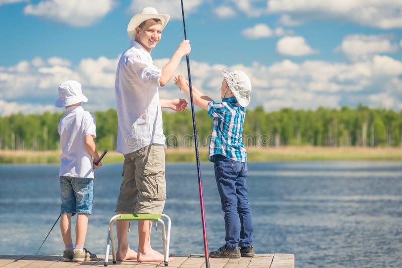 Père heureux avec les fils en voyage de pêche, portrait dans le plein lengt image stock