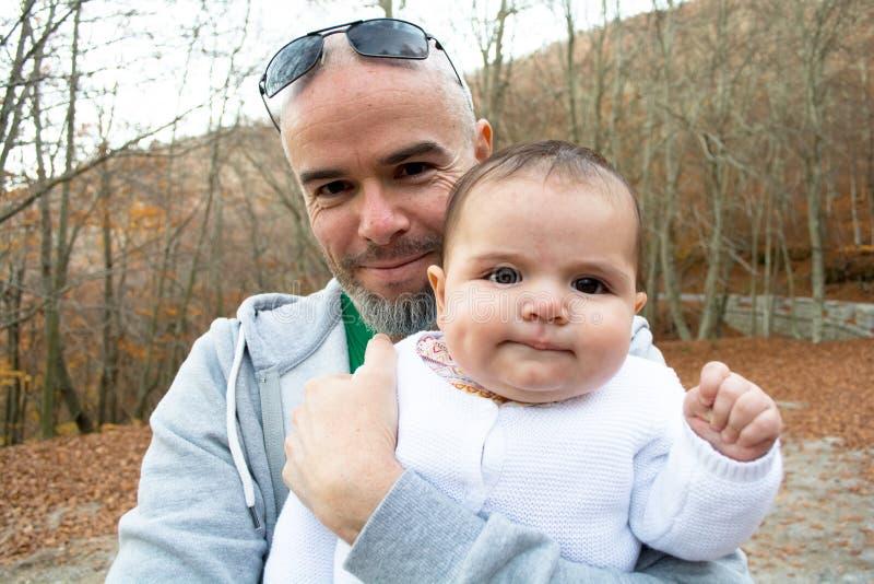 Père heureux avec son bébé pendant l'automne photos stock