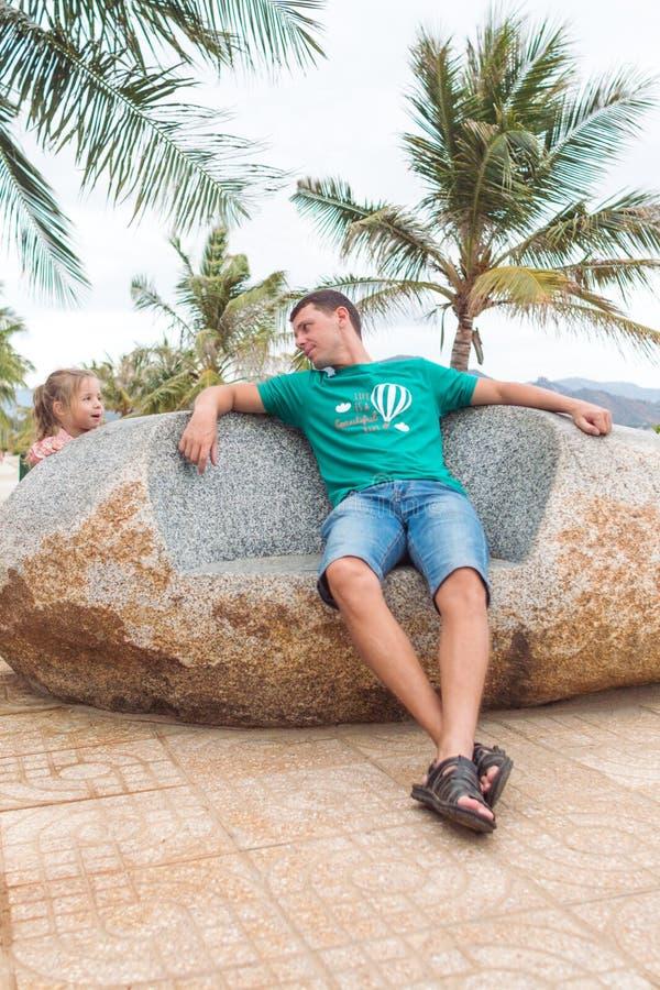 Père heureux avec un enfant s'asseyant sur la pierre près de la plage, ils jouent et sourient photographie stock