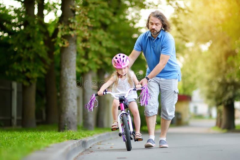 Père heureux enseignant sa petite fille à monter une bicyclette Enfant apprenant à monter un vélo images libres de droits