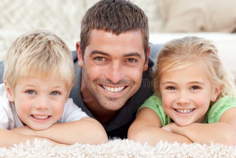 Père heureux et enfants se trouvant sur l'étage image stock