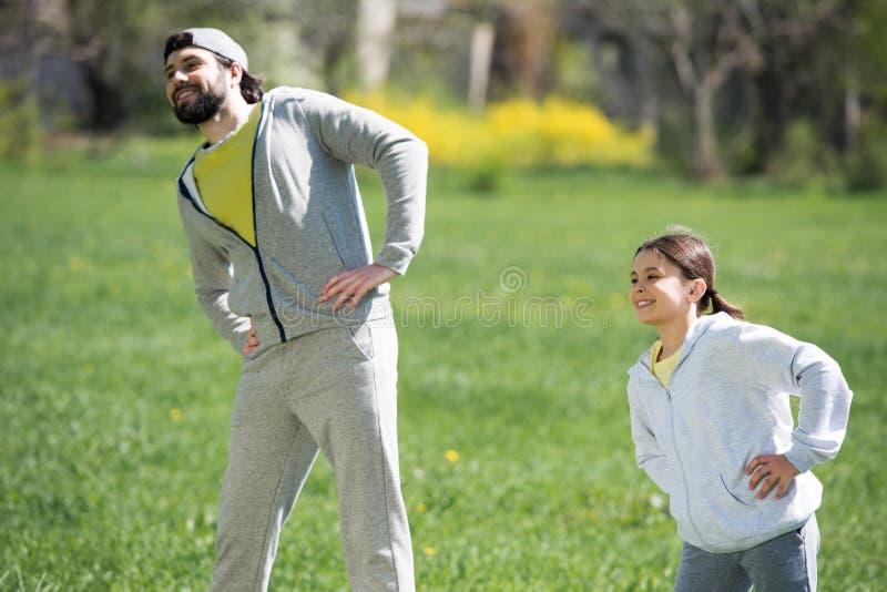 père heureux et fille faisant l'exercice physique photo stock