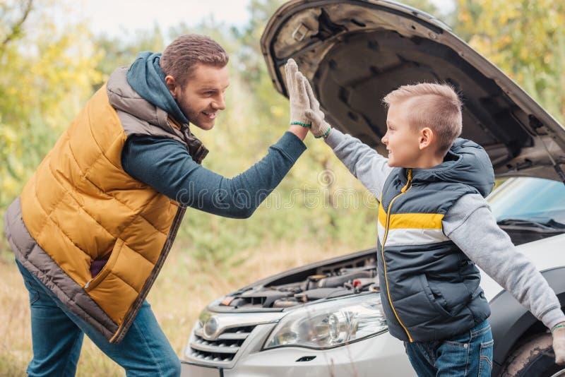 père heureux et fils donnant la haute cinq tout en réparant la voiture images libres de droits